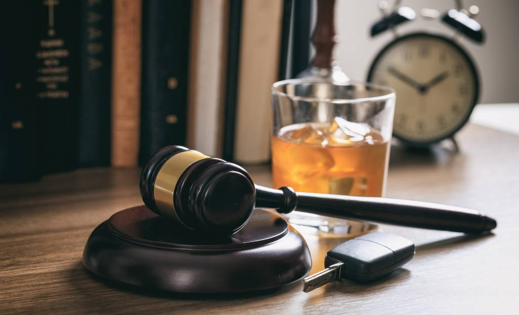 DUI concept. Law gavel alcohol and car keys on a wooden desk dark background